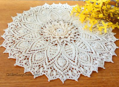 Crocheted doily and yellow flowers.
