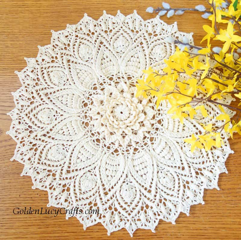 Crochet doily laying on the table, yellow flowers
