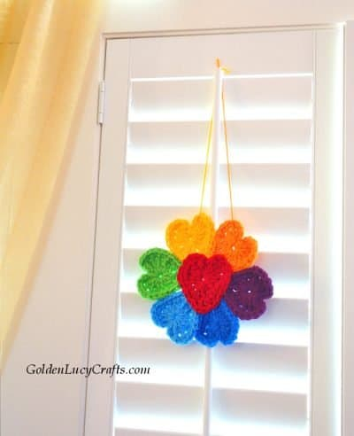 Crocheted flower made from hearts in rainbow colors hanging on the window.