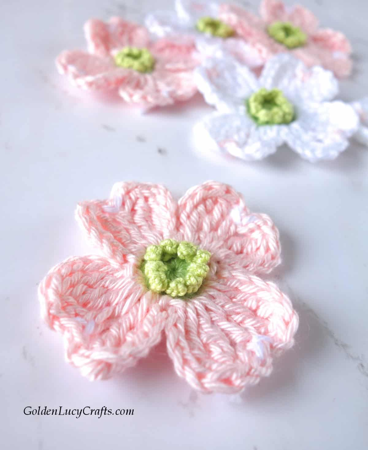 Crochet pink dogwood flower close up image.