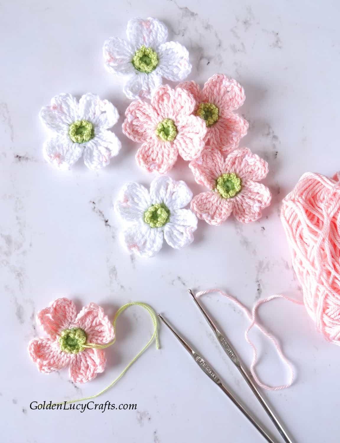 Crocheting dogwood flowers, crochet hooks, skein of pink yarn.