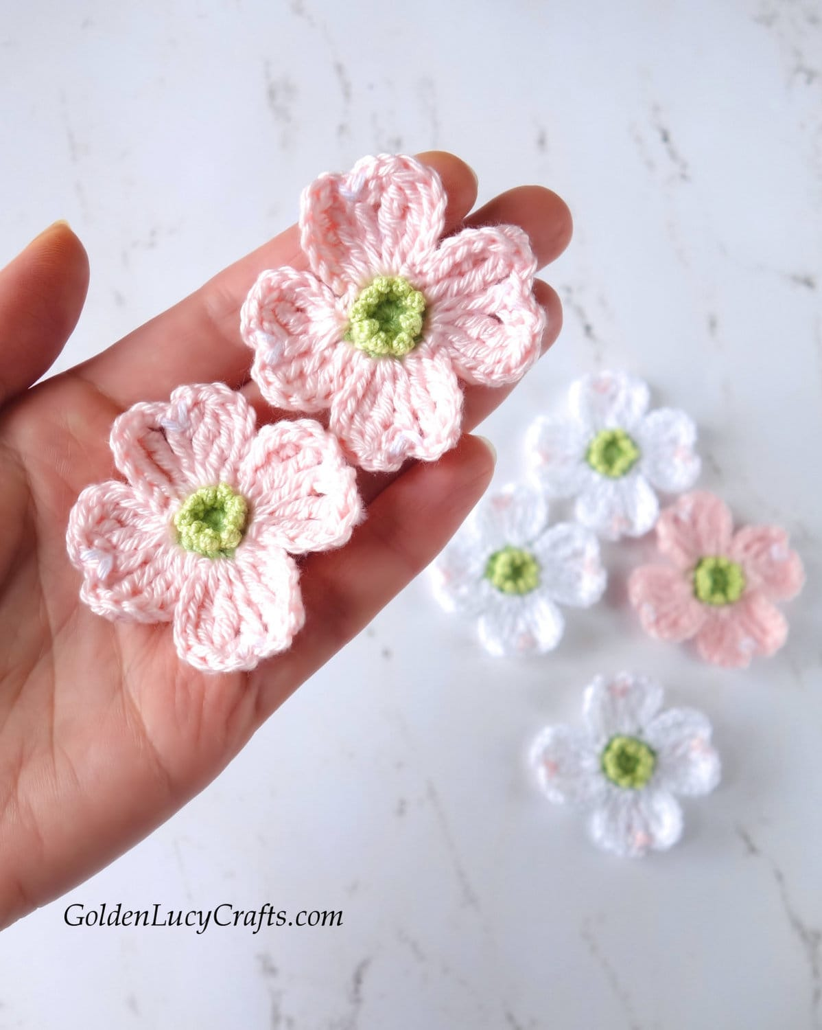 Crochet pink dogwood tree flowers in the palm of a hand.