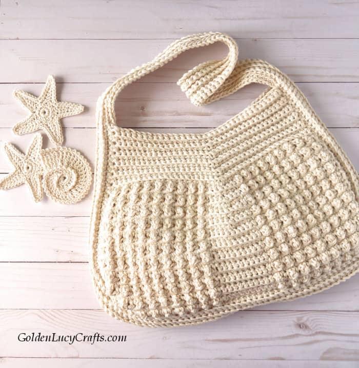 Crochet handbag, crochet appliques laying next to it