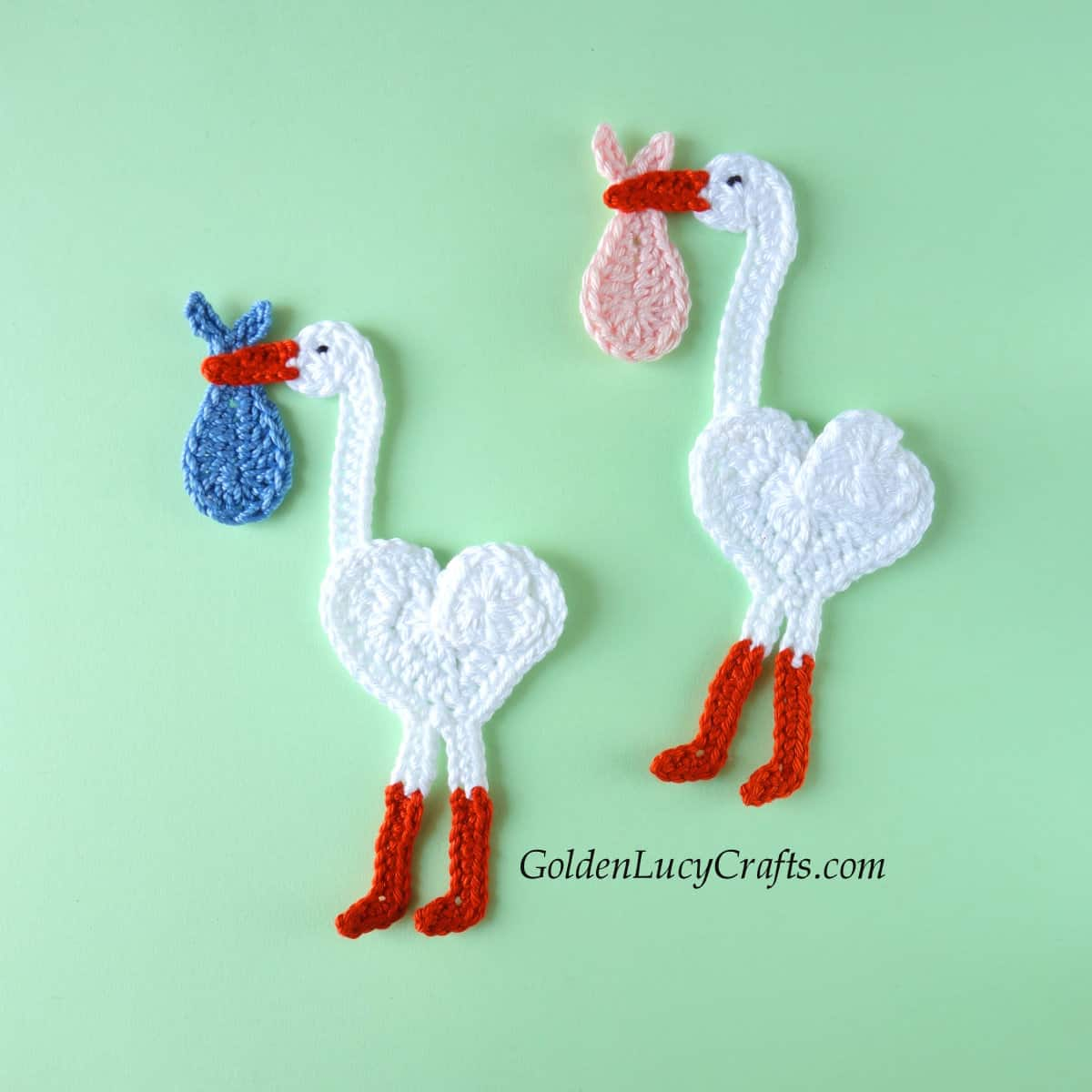 Two crocheted stork appliques.
