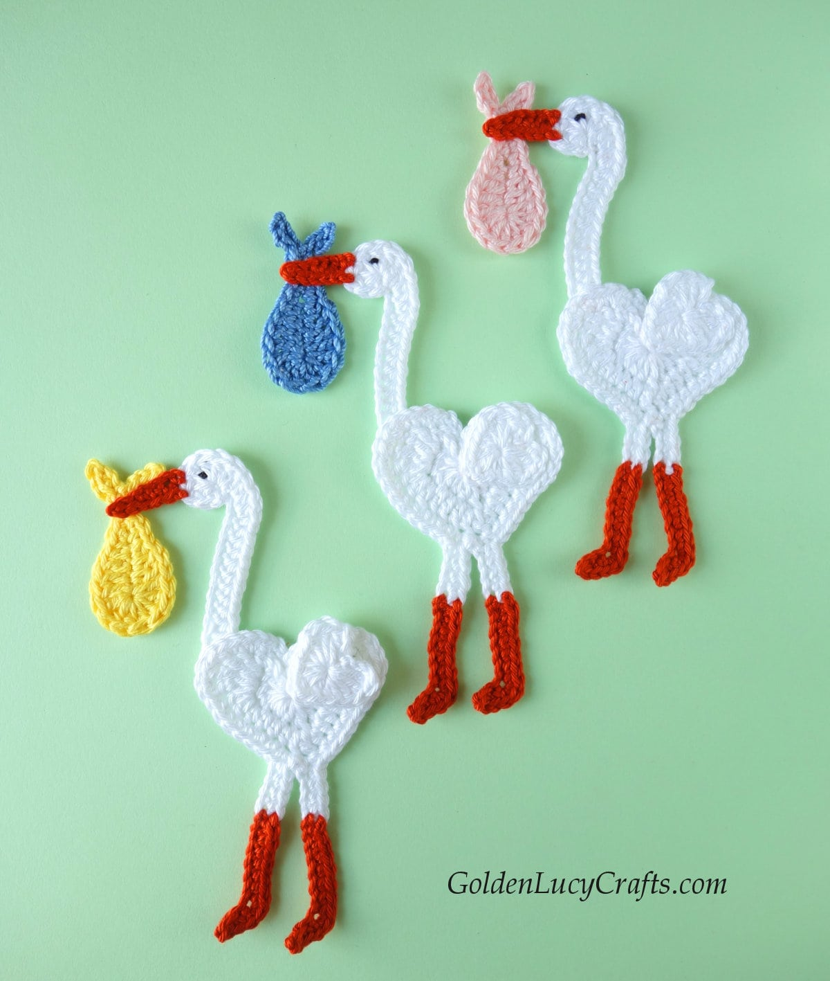 Crocheted appliques -  three storks carrying baby bundles.