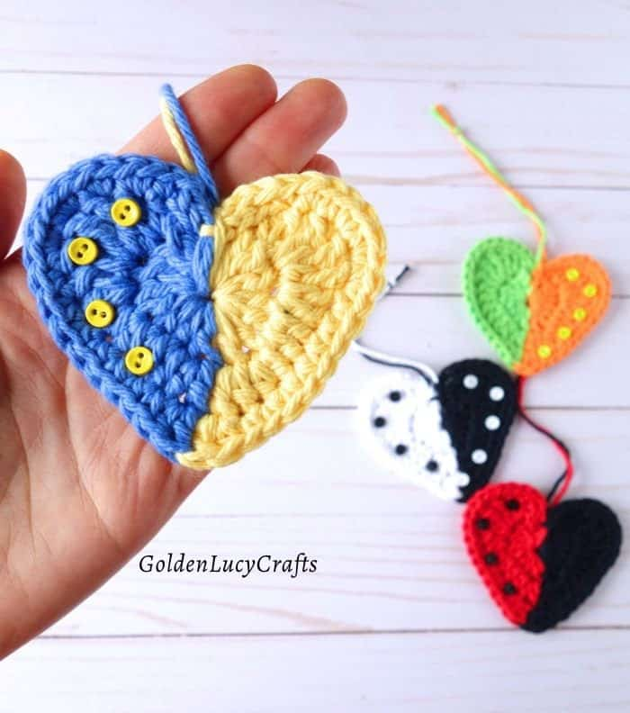 Yellow and blue crochet heart in the palm of the hand