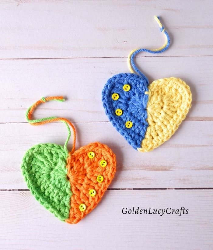 Two crocheted hearts in green and orange, blue and yellow colors.