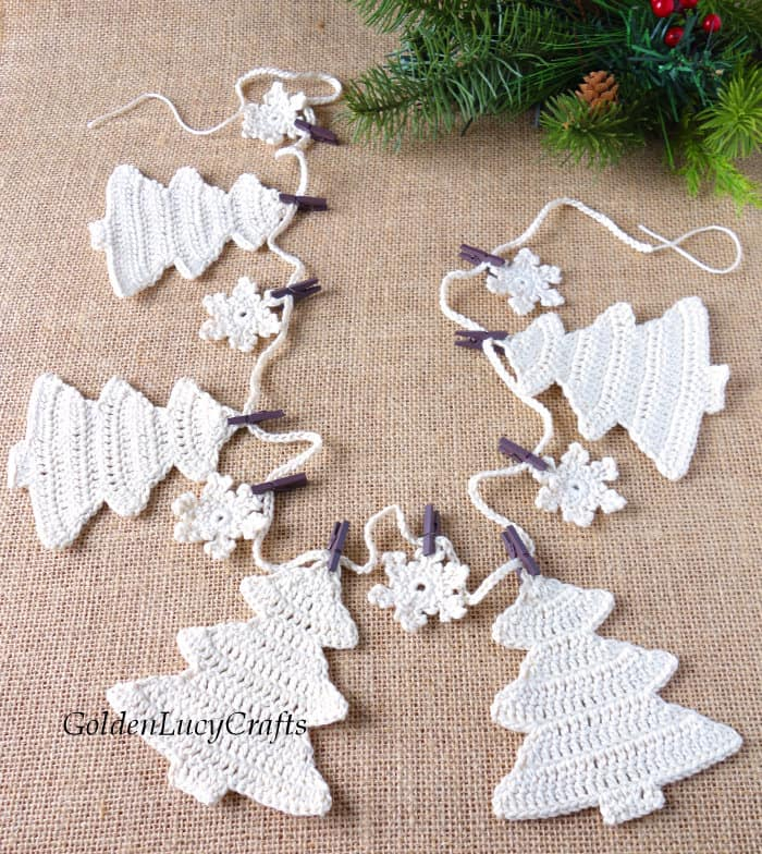 Christmas tree crochet garland in neutral color laying flat on the table