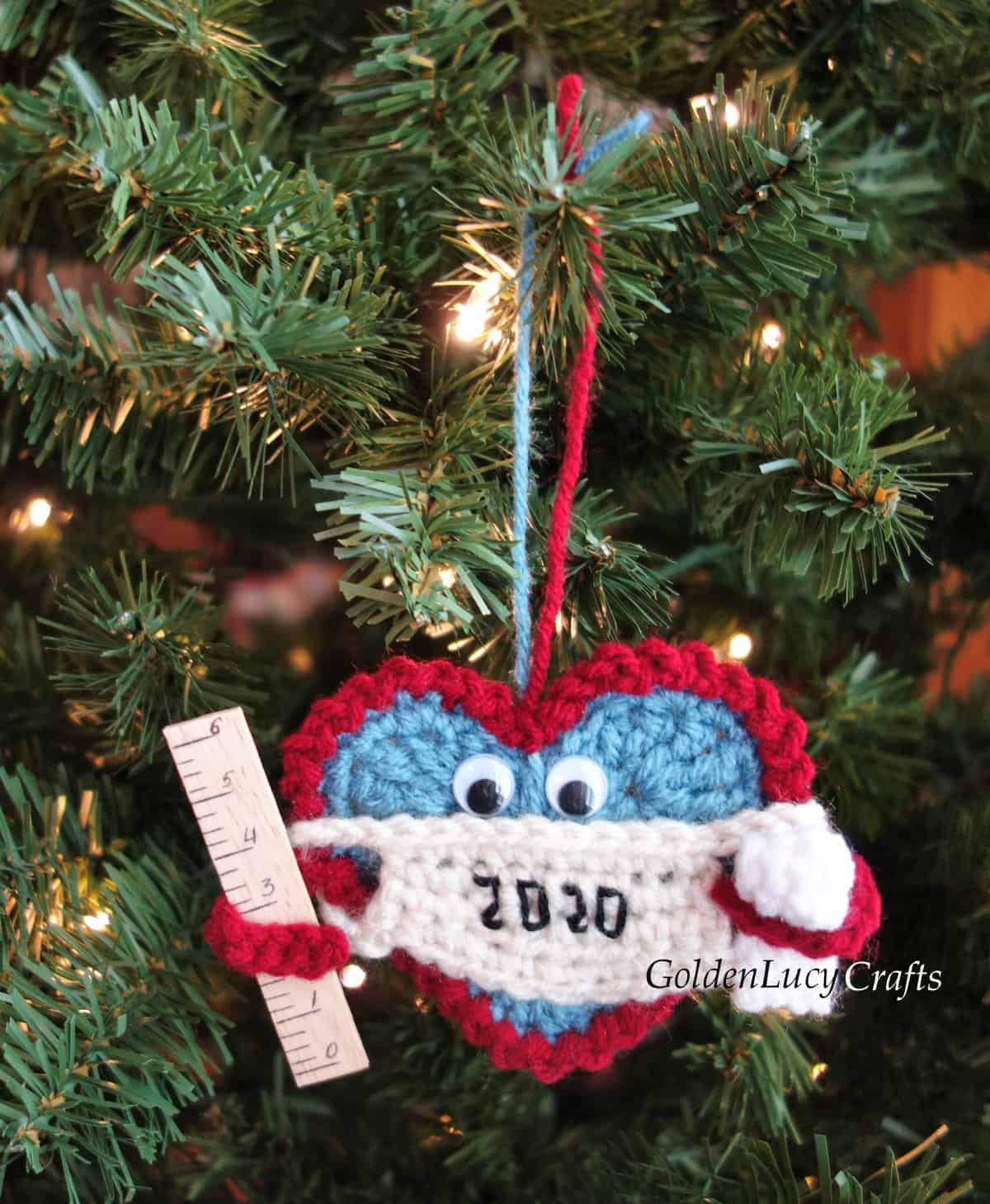 Crochet Christmas 2020 ornament hanging on the Christmas tree. The ornament is a Heart wearing a mask and holding a ruler in one arm and a toilet paper roll in the other.