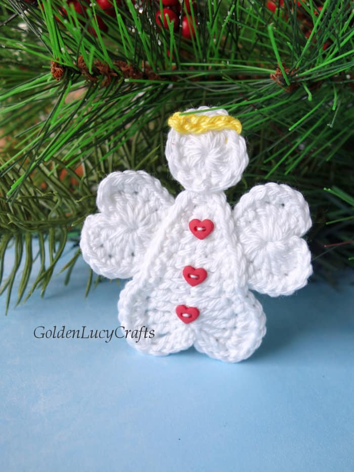 Crochet heart angel applique near the Christmas tree branch