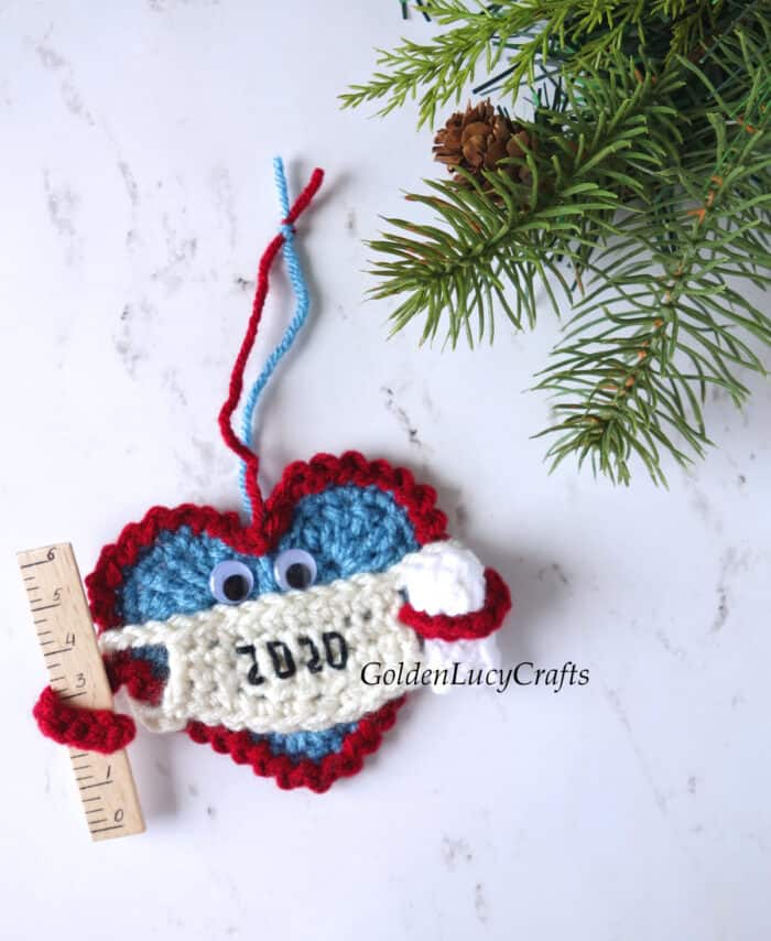 Crochet Christmas 2020 ornament. The ornament is a Heart wearing a mask and holding a ruler in one arm and a toilet paper roll in the other.