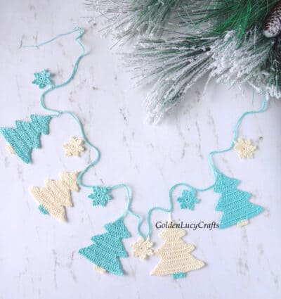 Crochet Christmas tree garland in turquoise and cream color laying flat on the table