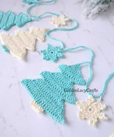 Crochet Christmas tree garland in turquois and cream, close up image