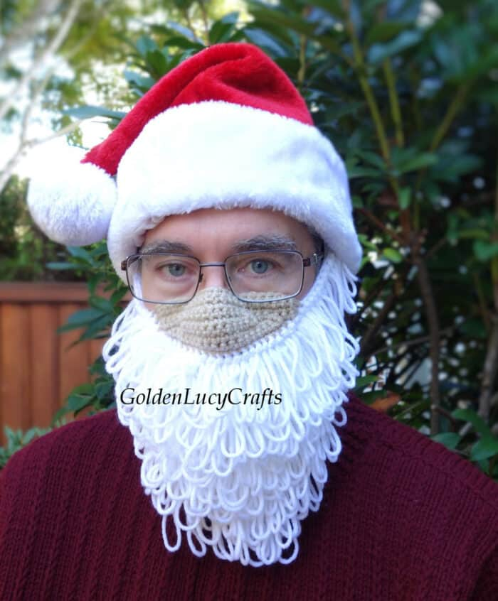 Model is wearing Santa beard mask and Santa hat