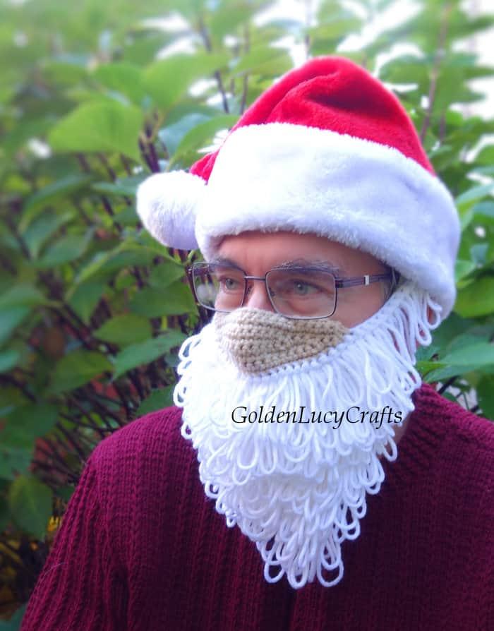 Model is wearing crocheted Santa  beard mask