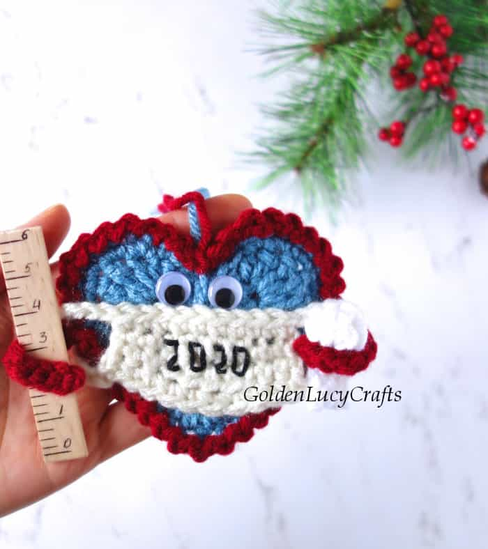 Christmas 2020 ornament in the palm of a hand. The ornament is a Heart wearing a mask and holding a ruler in one arm and a toilet paper roll in the other.