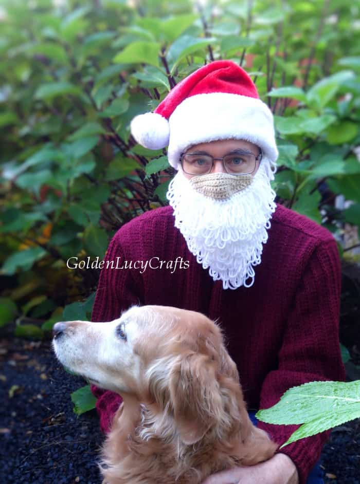 Golden retriever with man, dressed in Santa beard mask and Santa hat