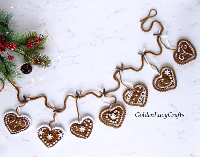 Crocheted gingerbread hearts garland laying on the flat surface