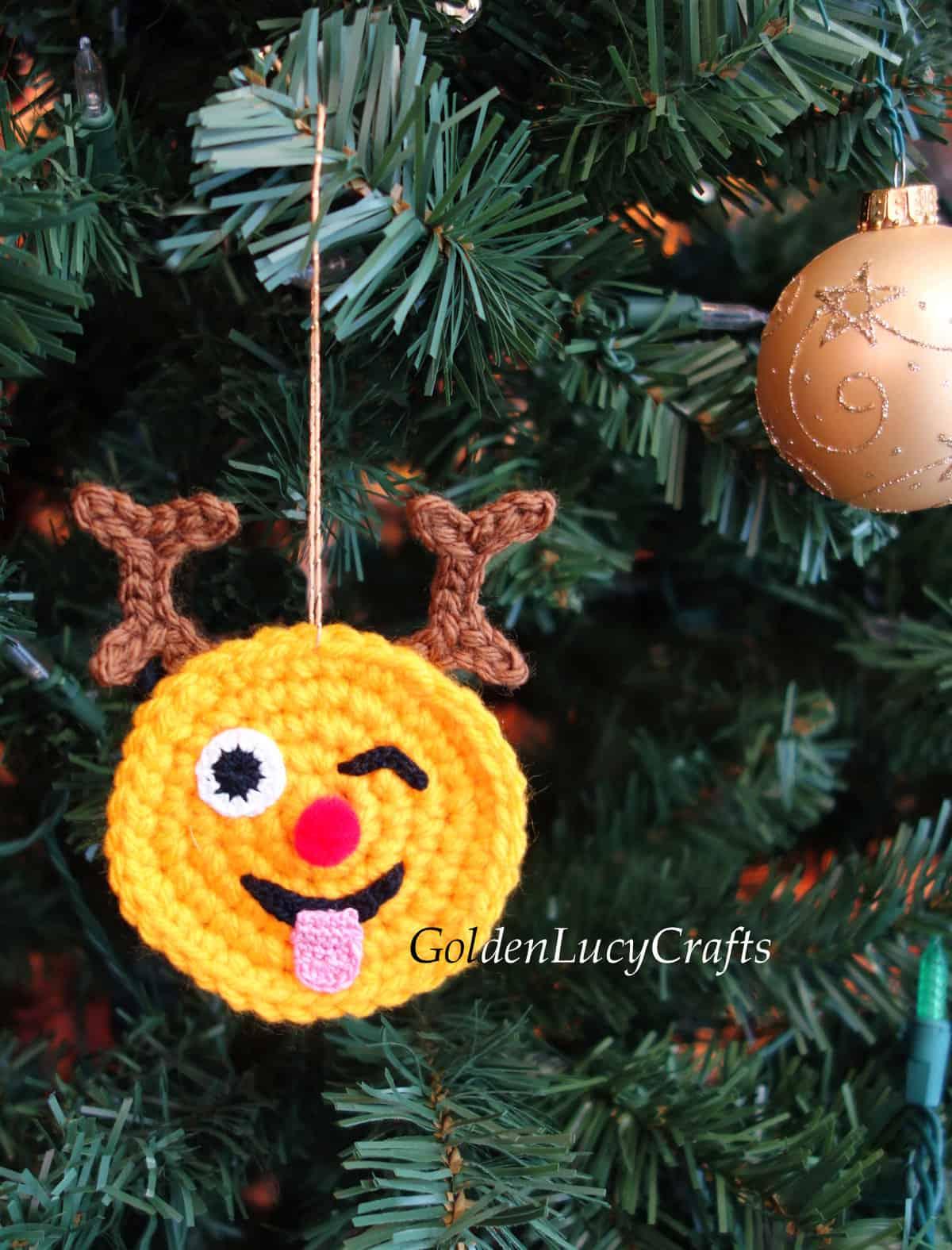 Crochet reindeer emoji ornament hanging on Christmas tree.