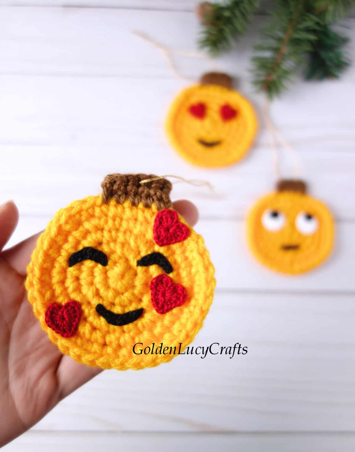 Crochet emoji ornament in the palm of a hand