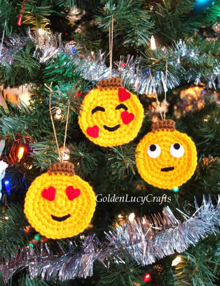 Crochet emoji ornaments hanging on the Christmas tree.
