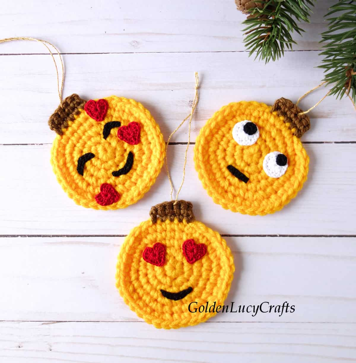 Three crochet emoji Christmas ornaments laying flat on the surface.