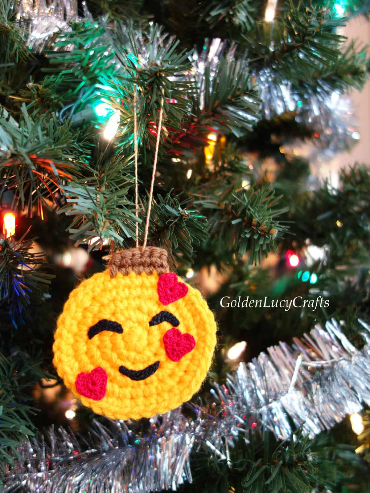 Crochet smiling face emoji ornament hanging on the Christmas tree.
