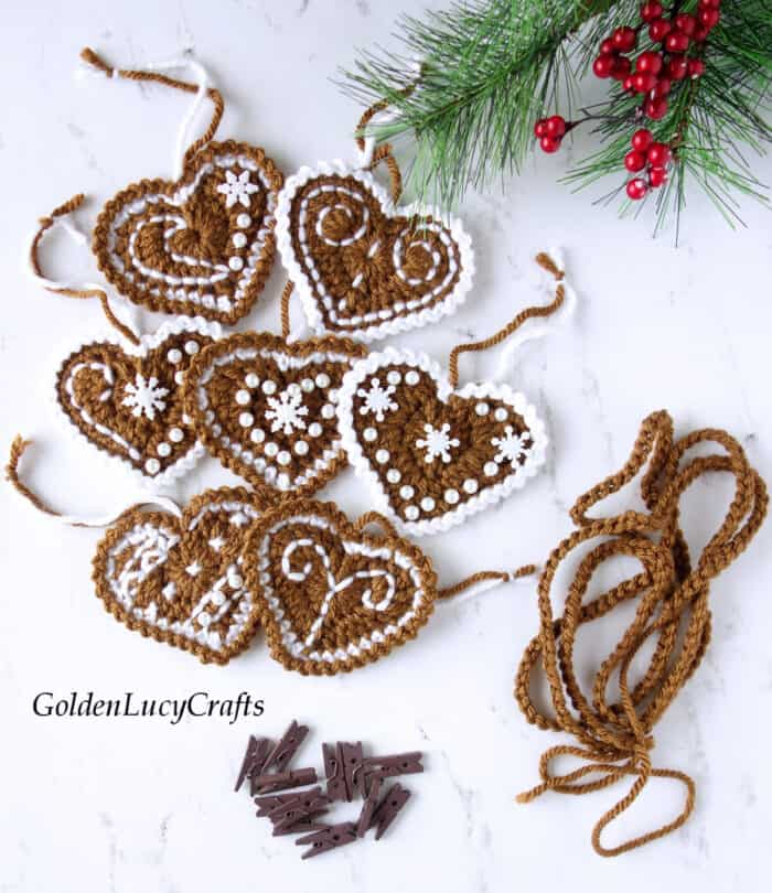 Crocheted gingerbread hearts, crocheted rope, brown clothespins laying on the table