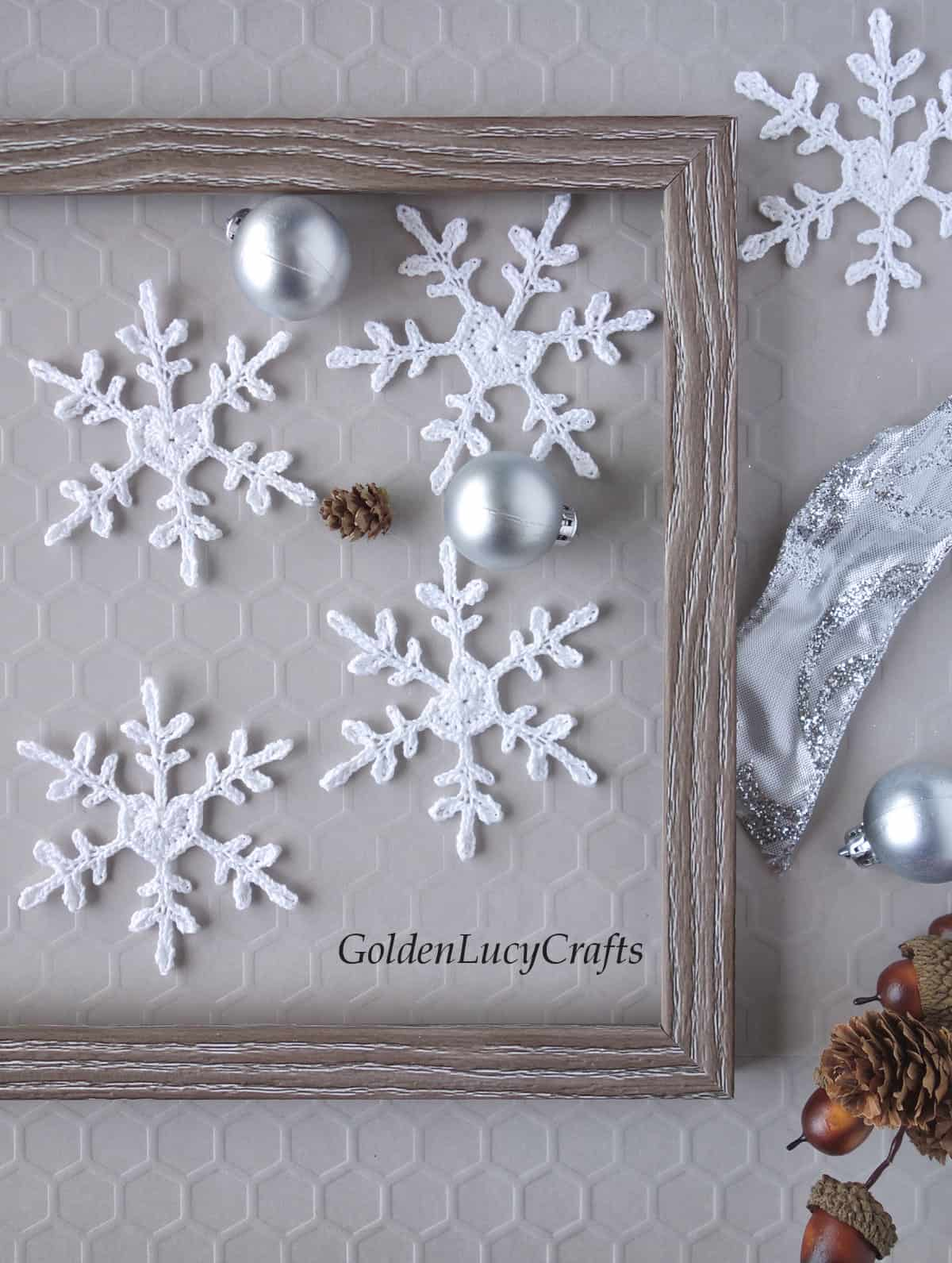 Crochet white snowflakes with heart center, small silver Christmas ball ornaments and small pinecone  laying inside of picture frame