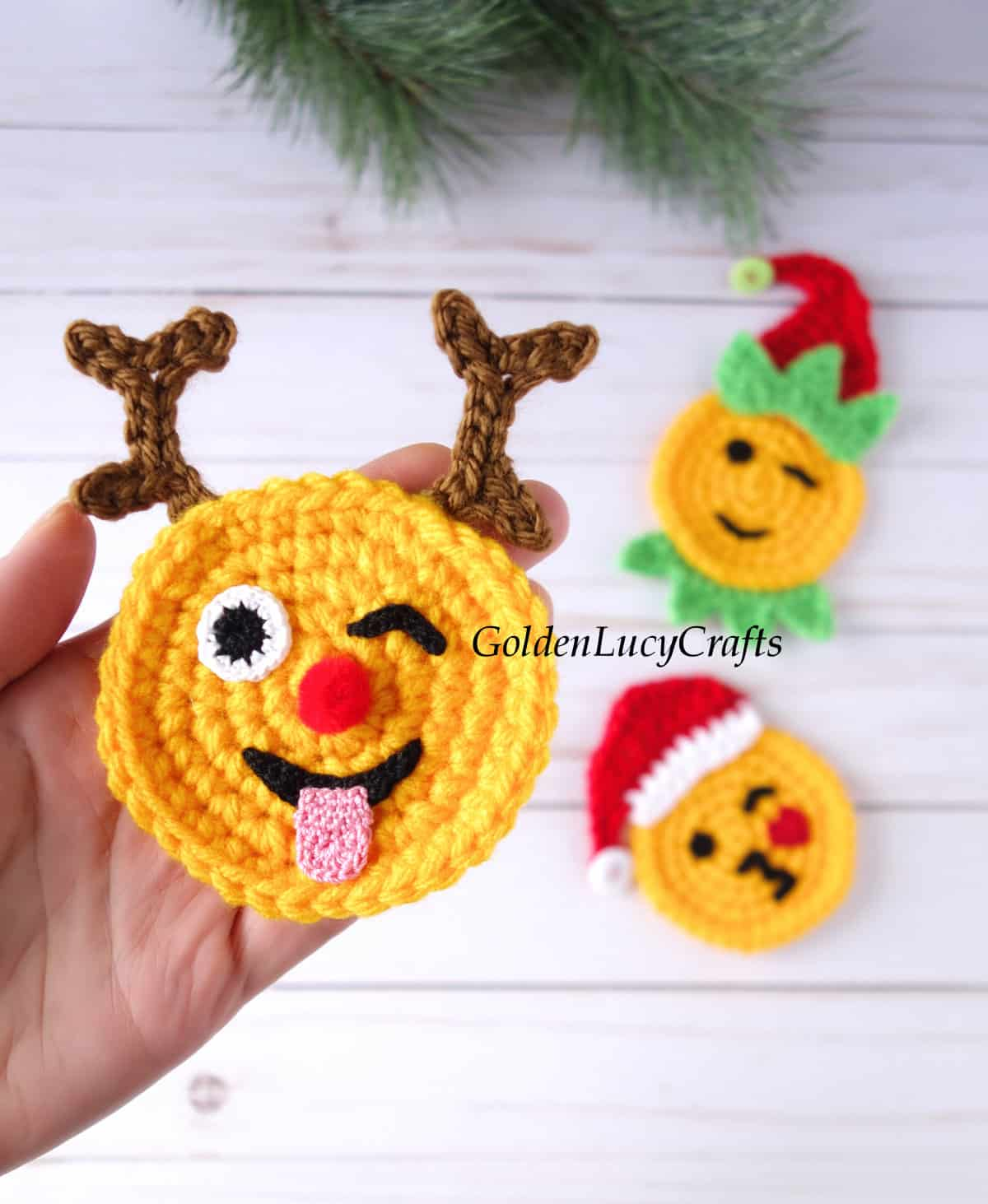 Crochet reindeer emoji in the palm of a hand.