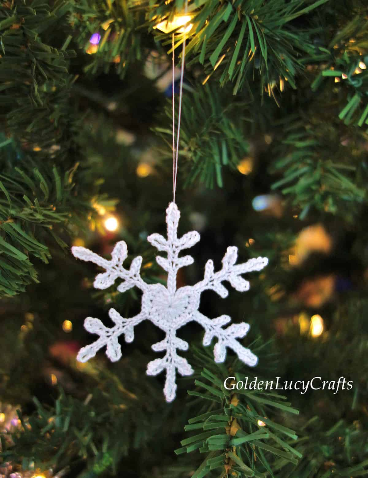 Crochet heart snowflake hanging on the Christmas tree.