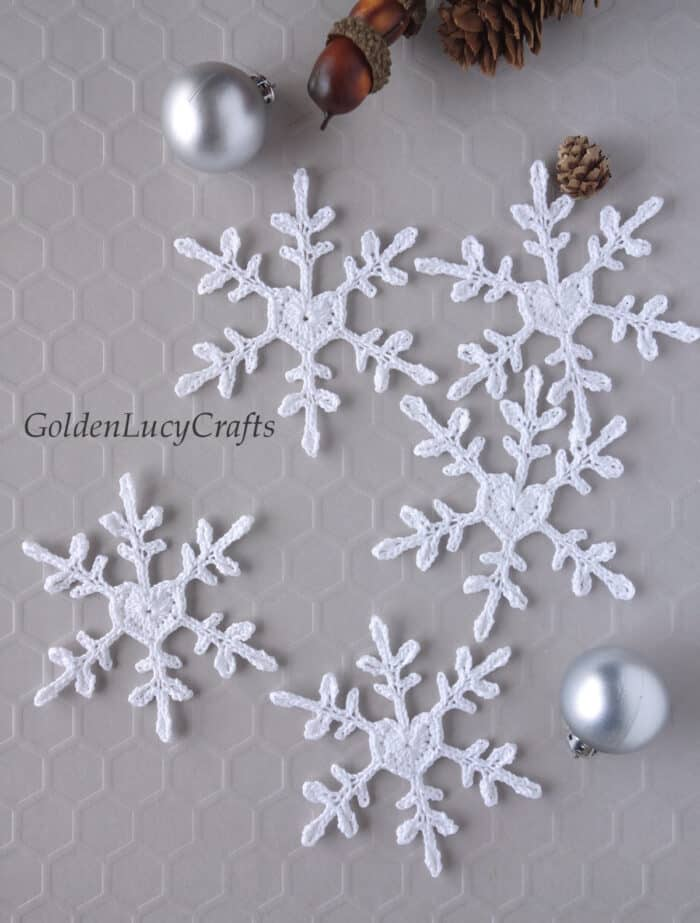 Crochet white snowflakes with heart center, small silver Christmas ball ornaments, small pinecone.