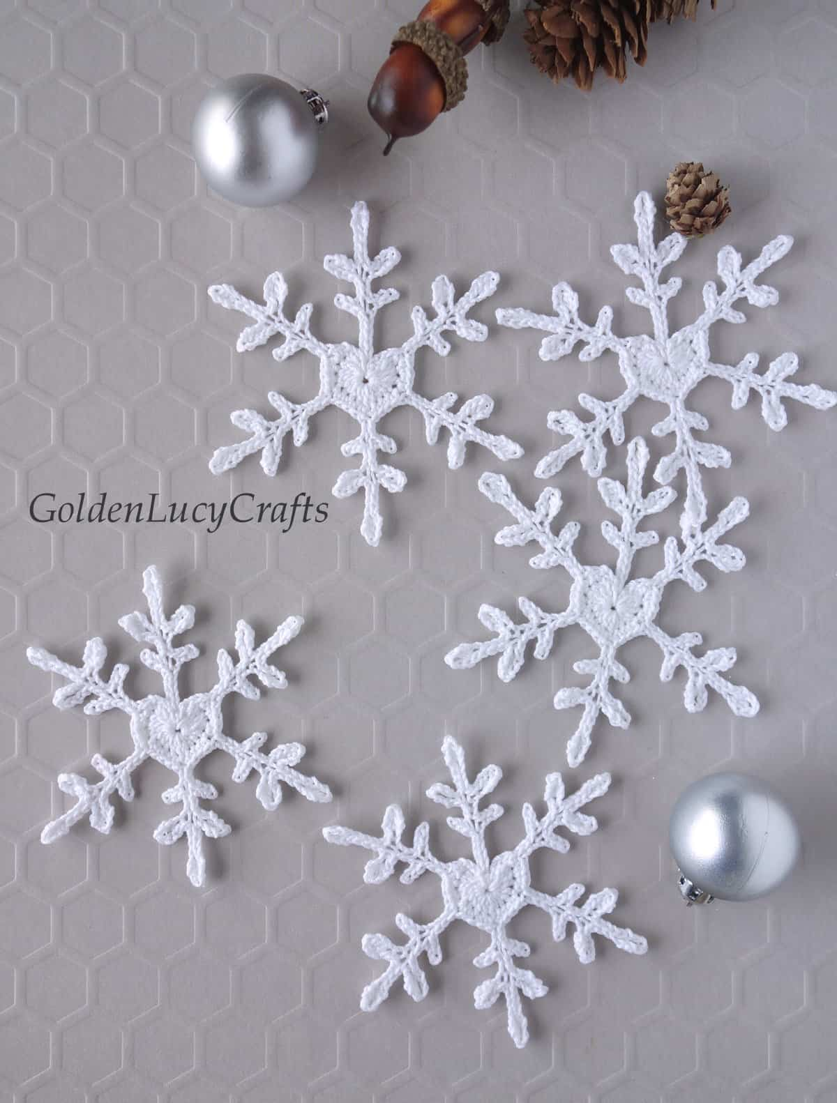 Crochet white snowflakes with heart center, small silver Christmas ball ornaments, small pinecone and acorns.