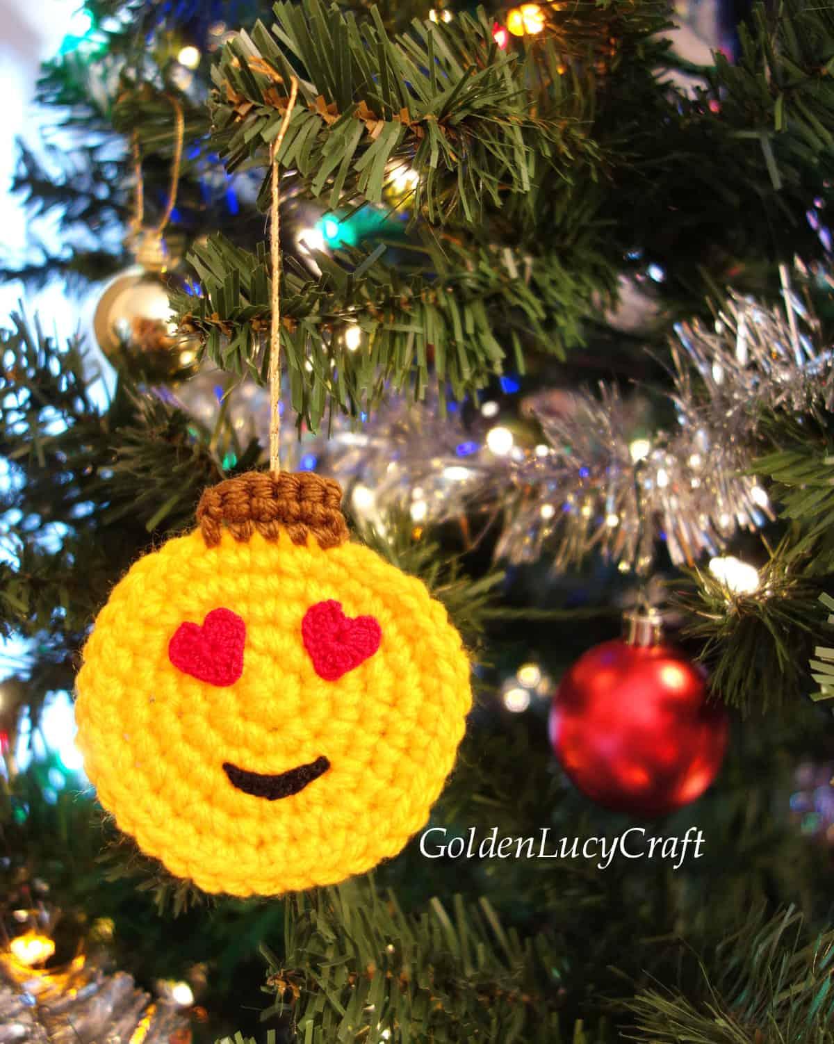 Crochet heart eyes emoji Christmas ornament hanging on the Christmas tree.