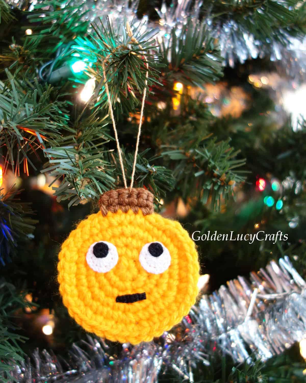 Crochet rolling eyes emoji Christmas ornament hanging on the Christmas tree.