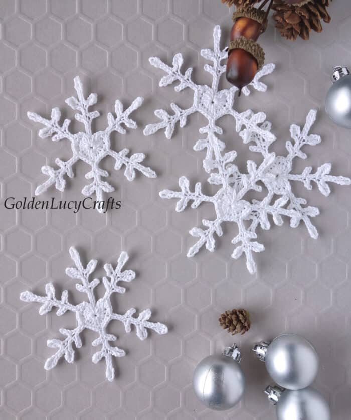 Crochet white snowflakes with heart center, small silver Christmas ball ornaments, small acorns and pinecones.