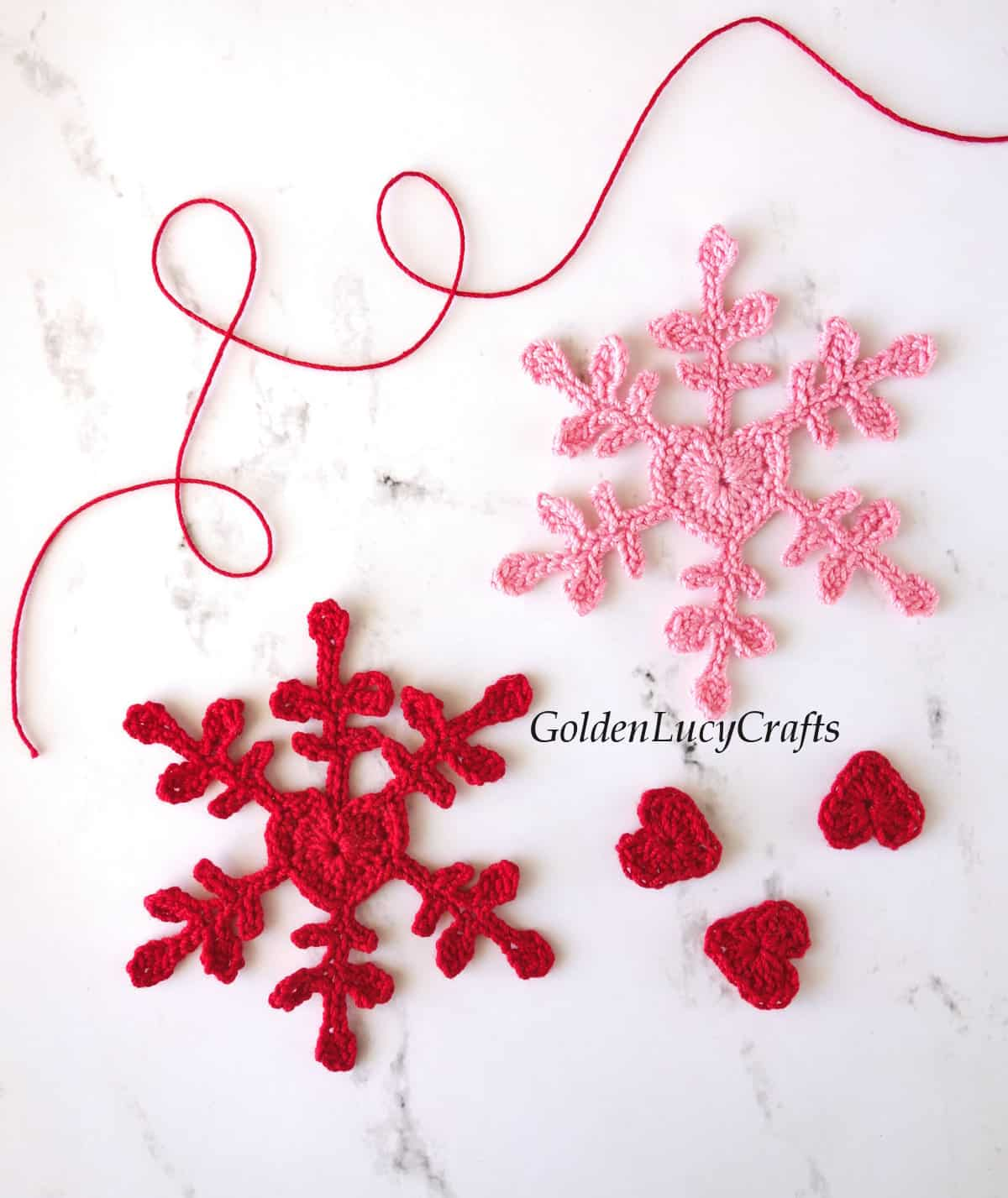 Red and pink crocheted snowflakes with heart center, three small red hearts