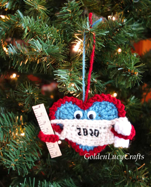 Crochet heart-shaped Christmas 2020 ornament hanging on the Christmas tree.