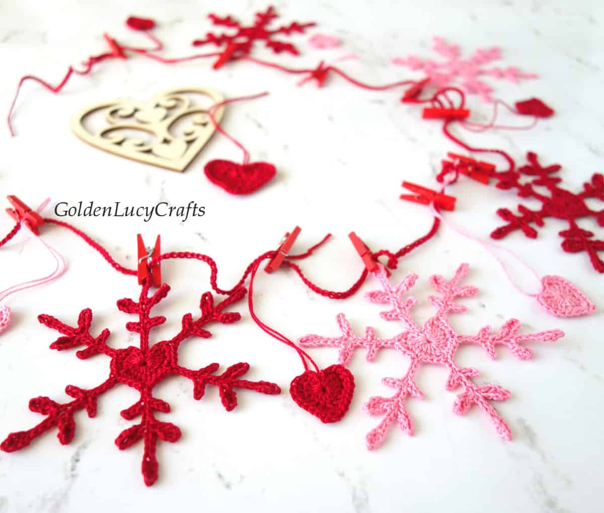 Crochet Valentines Day garland made from snowflakes and hearts in red and pink colors.