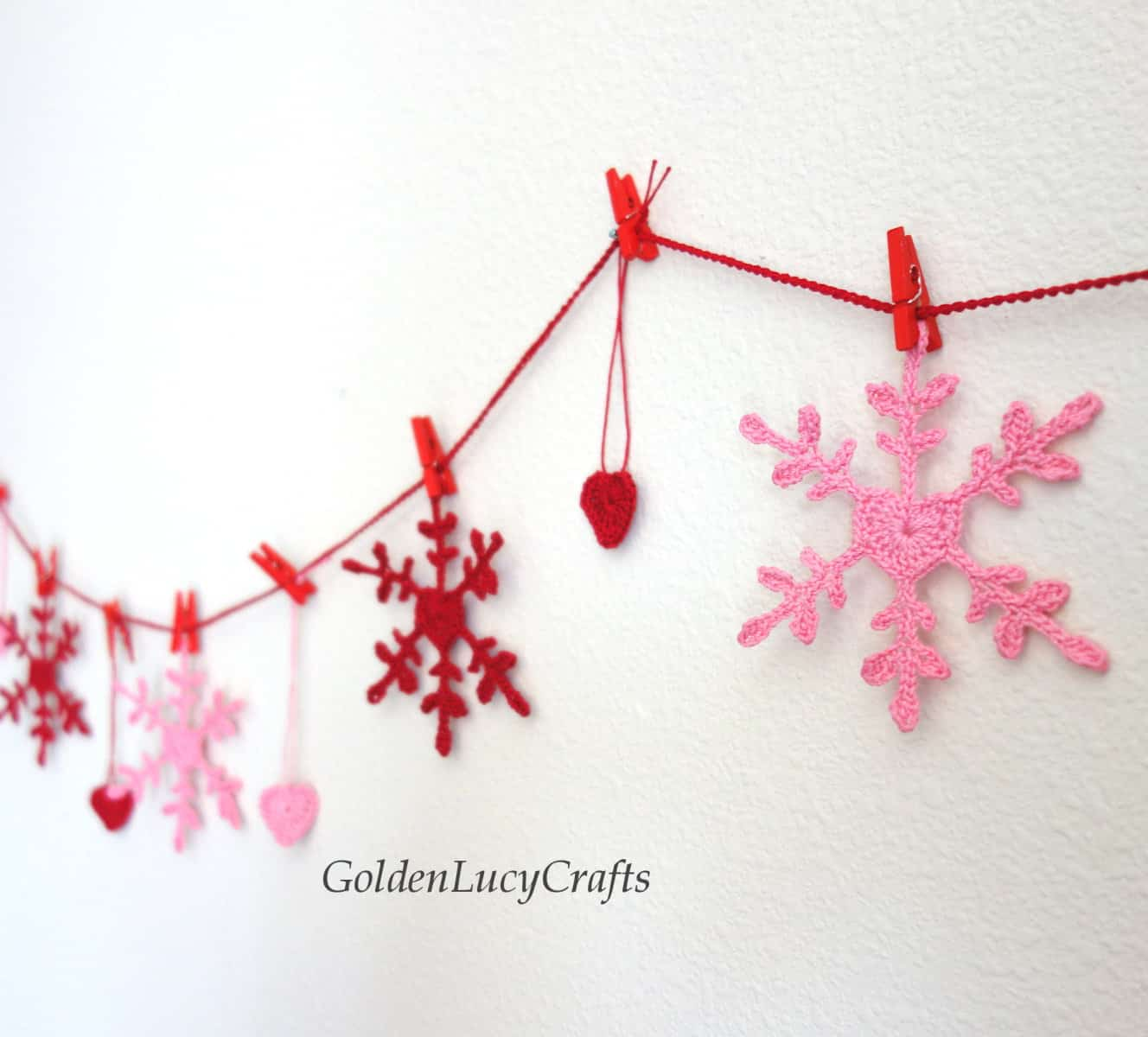 Crochet Valentine's Day bunting hanging on the wall.
