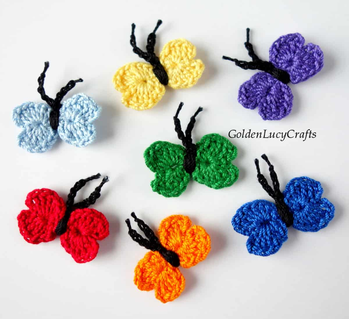Seven small crocheted butterfly appliques in colors of rainbow.