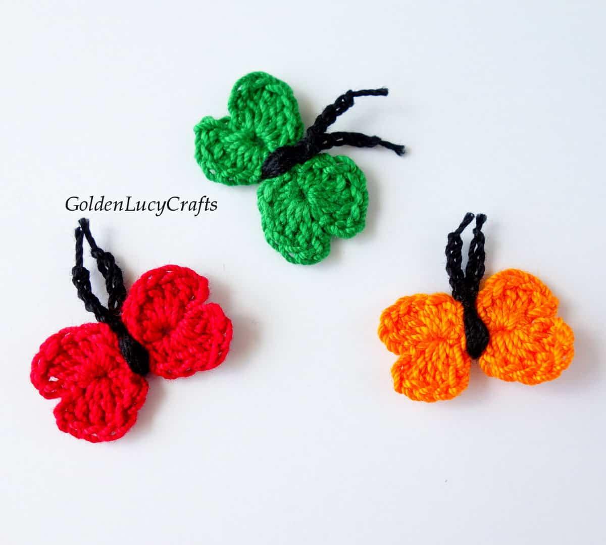 Three crochet butterflies in red, orange and green.