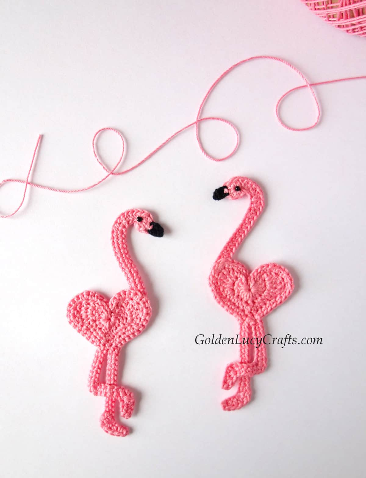 Two crocheted flamingo appliques.