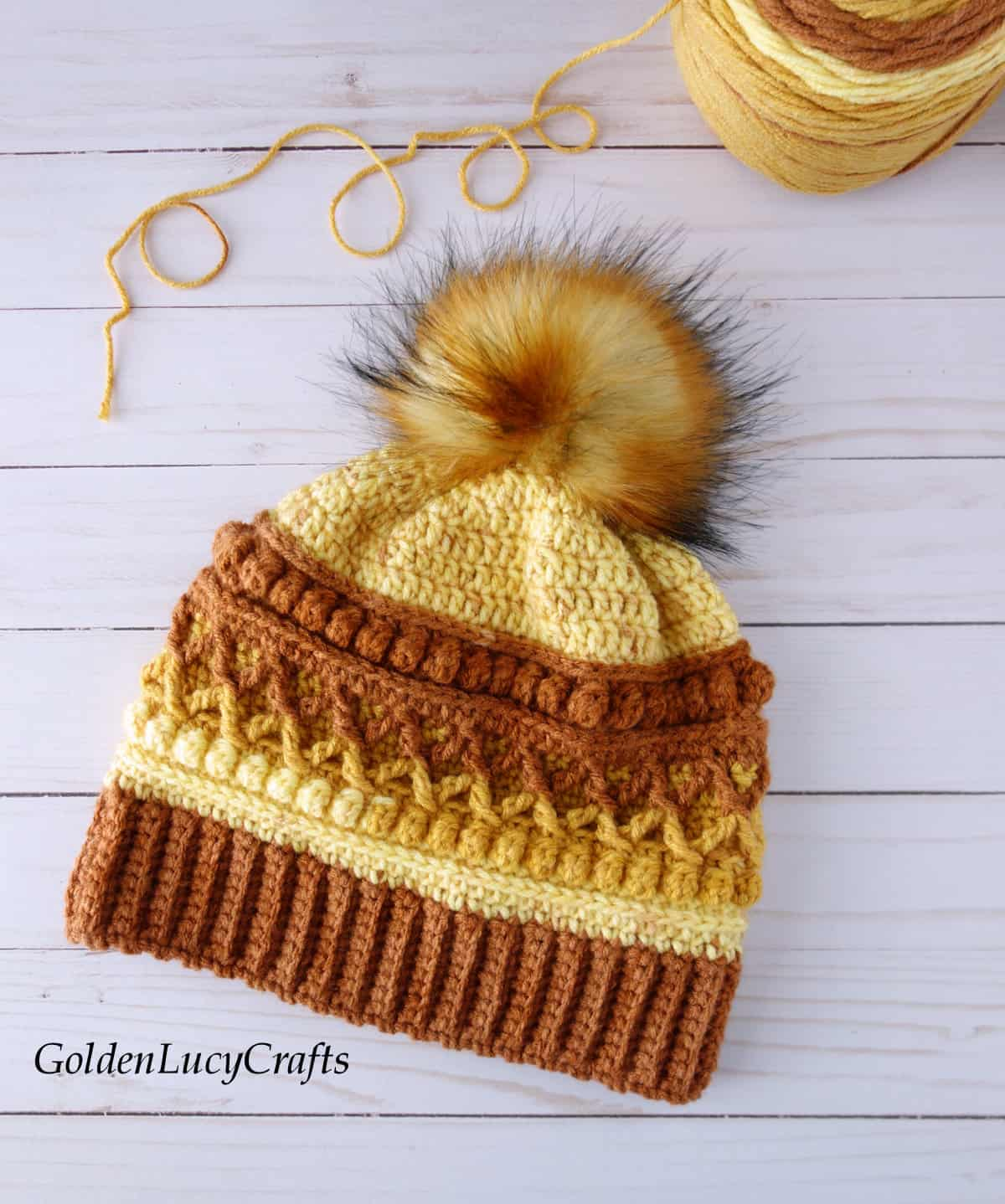 Crocheted hat in brown, orange and yellow colors embellished with faux fur pompom, ball of yarn in the background.