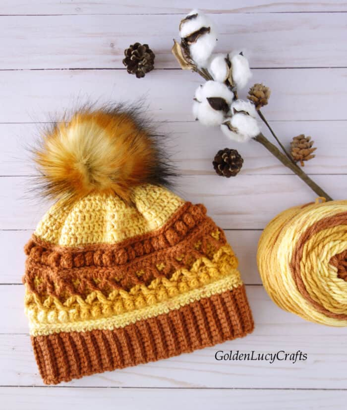 Crocheted hat in brown, orange and yellow colors embellished with fur pompom, ball of yarn, cotton branch, pine cones are laying on the flat surface.