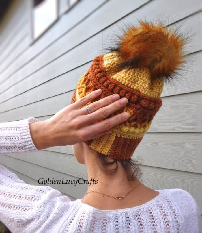 Women dressed in crocheted hat, view from the back.