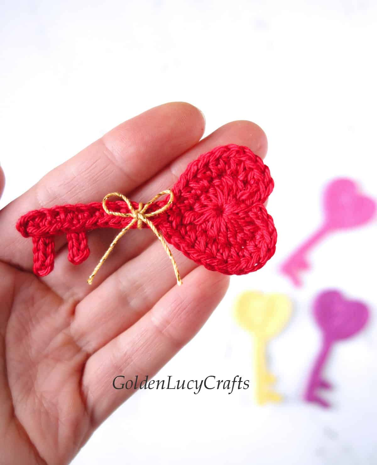 Crochet heart-shaped key applique in the palm of a hand.