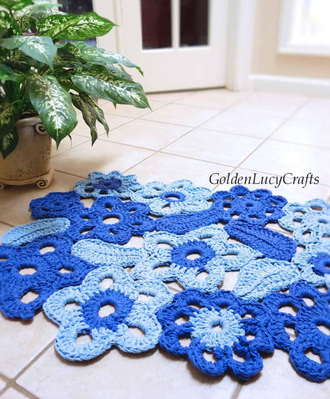 Crochet flower rug laying on the tile floor.