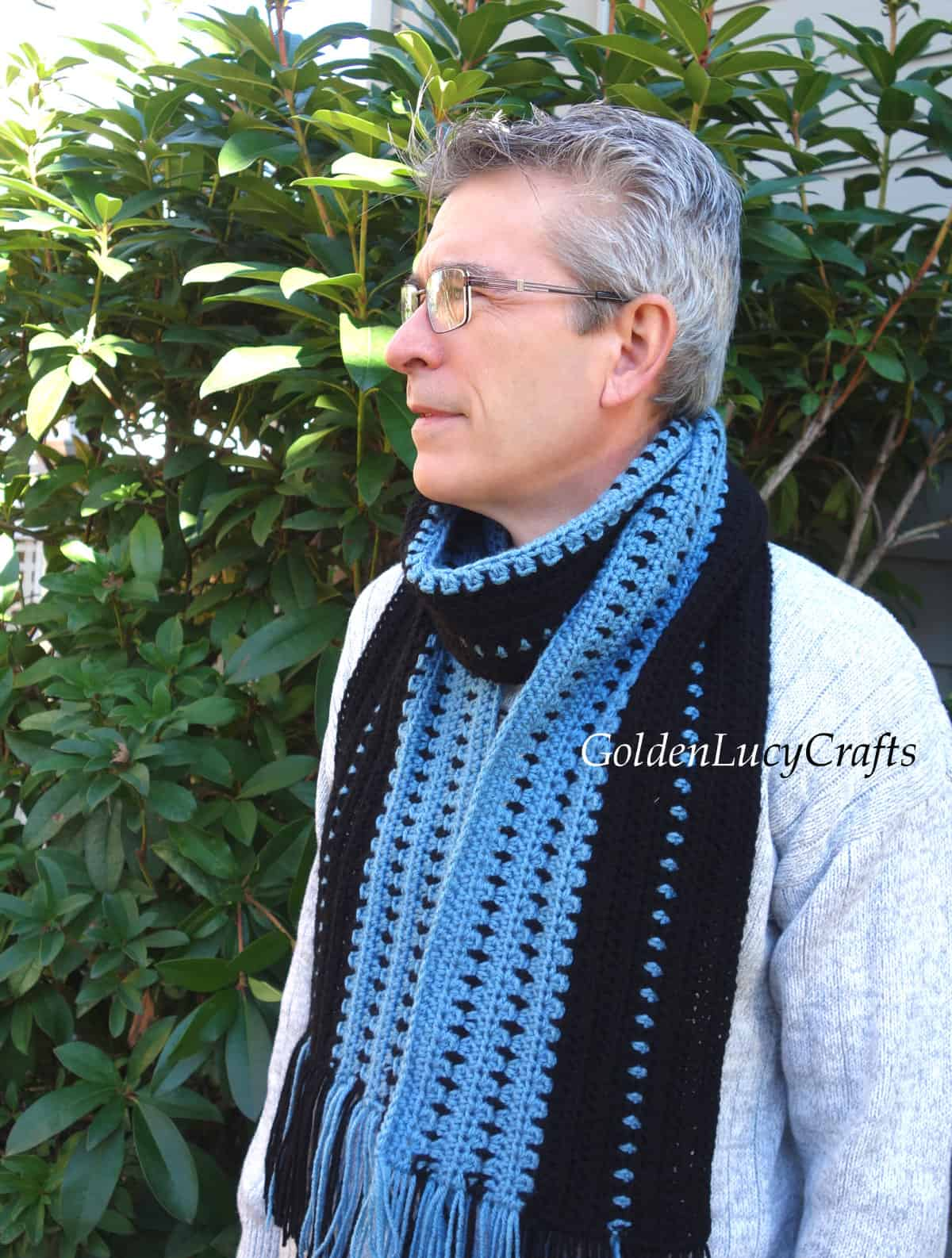 Men dressed in crocheted scarf in blue and black colors.