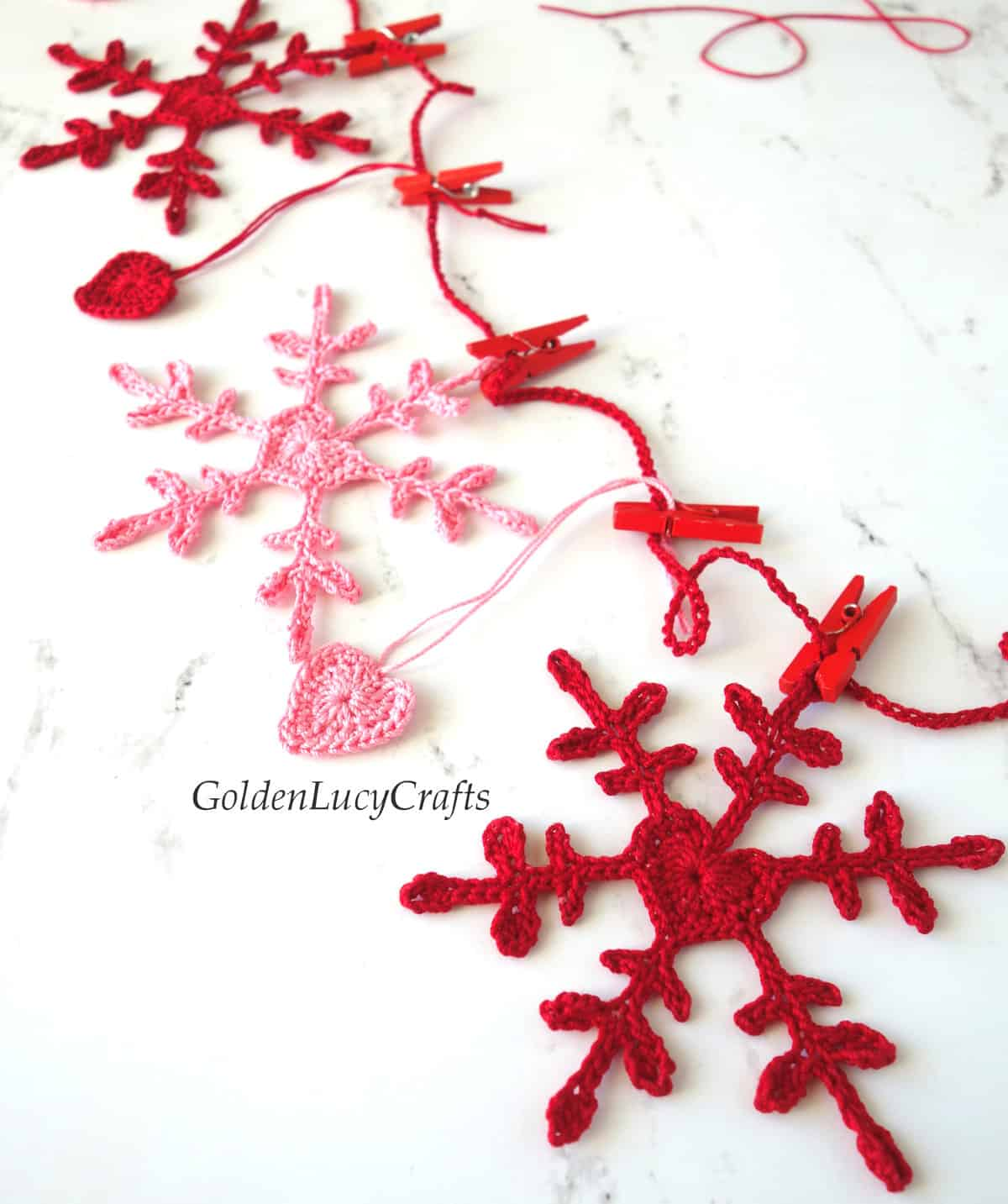 Crochet Valentines Day garland made from snowflakes and hearts in red and pink colors, close up image.
